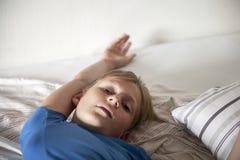 muchacho en una cama foto de archivo