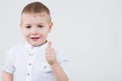 Muchacho en una camisa blanca que hace los pulgares para arriba Imágenes de archivo libres de regalías