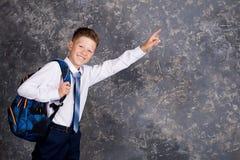 Muchacho en una camisa blanca y lazo con una mochila imagen de archivo libre de regalías