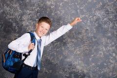 Muchacho en una camisa blanca y lazo con una mochila fotos de archivo