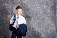 Muchacho en una camisa blanca y lazo con una mochila imagenes de archivo