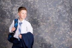 Muchacho en una camisa blanca y lazo con una mochila fotos de archivo libres de regalías