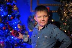 Muchacho en una camisa del dril de algodón contra del árbol de navidad Imagenes de archivo
