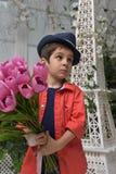 muchacho en una camisa roja y un sombrero con un ramo de tulipanes adentro Imagen de archivo