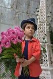 muchacho en una camisa roja y un sombrero con un ramo de tulipanes adentro Fotografía de archivo libre de regalías