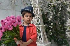 muchacho en una camisa roja y un sombrero con un ramo de tulipanes adentro Imagen de archivo libre de regalías