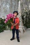muchacho en una camisa roja y un sombrero con un ramo de tulipanes adentro Imagenes de archivo