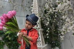 muchacho en una camisa roja y un sombrero con un ramo de tulipanes adentro Fotos de archivo