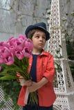 muchacho en una camisa roja y un sombrero con un ramo de tulipanes adentro Fotografía de archivo