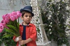 muchacho en una camisa roja y un sombrero con un ramo de tulipanes adentro Foto de archivo
