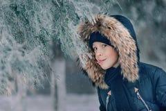 Muchacho en una chaqueta con una capilla en un parque nevoso Fotografía de archivo