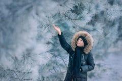 Muchacho en una chaqueta con una capilla en un parque nevoso Foto de archivo libre de regalías