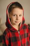 Muchacho en una chaqueta roja con una capilla Fotografía de archivo