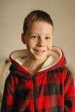 Muchacho en una chaqueta roja con una capilla Foto de archivo libre de regalías