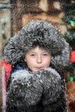 Muchacho en una chaqueta y un sombrero de piel en la Navidad con los copos de nieve Imagen de archivo