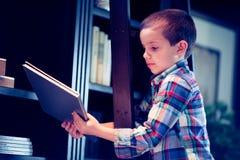 Muchacho en una escalera con el libro en la biblioteca Imagen de archivo libre de regalías