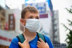 Muchacho en una máscara protectora en una calle en Pekín Foto de archivo libre de regalías