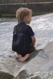 Muchacho en una piedra mojada grande Foto de archivo libre de regalías