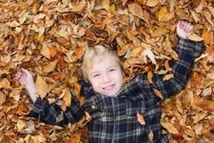 Muchacho en una pila de hojas Fotografía de archivo