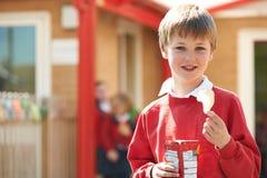 Muchacho en uniforme escolar que come la patata Chip In Playground Imagen de archivo