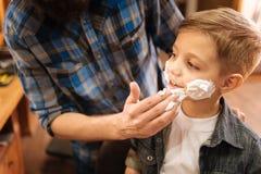 Muchacho encantado lindo que disfruta de su primer afeitar Imagen de archivo libre de regalías