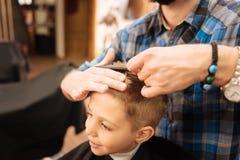 Muchacho encantado lindo que tiene los extremos de su corte del pelo Imagenes de archivo