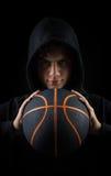 Muchacho encapuchado insolente que lleva a cabo baloncesto Imágenes de archivo libres de regalías