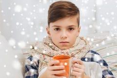 Muchacho enfermo con gripe en té de consumición de la bufanda en casa fotos de archivo