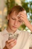 Muchacho enfermo con las píldoras Foto de archivo libre de regalías