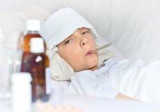 Muchacho enfermo que miente en cama Foto de archivo libre de regalías