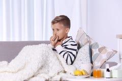 Muchacho enfermo que sufre de tos en el sofá imagenes de archivo