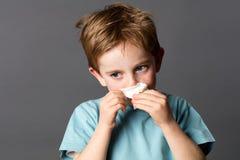 Muchacho enfermo que usa un tejido después de alergias del frío o de la primavera Imagenes de archivo