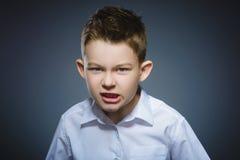 Muchacho enojado aislado en fondo gris primer Imagen de archivo