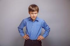Muchacho enojado del adolescente en fondo gris Fotografía de archivo