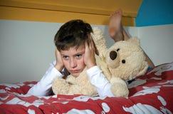 Muchacho enojado en cama Foto de archivo libre de regalías