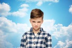 Muchacho enojado en camisa a cuadros sobre el cielo azul Fotografía de archivo
