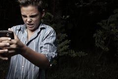 Muchacho enojado en su teléfono celular Foto de archivo libre de regalías