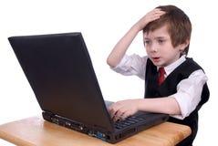 Muchacho enojado en un ordenador portátil Imagen de archivo libre de regalías