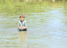 Muchacho enojado que se coloca en agua Foto de archivo libre de regalías