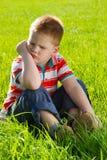 Muchacho enojado que se sienta en hierba Imagen de archivo libre de regalías