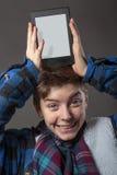 Muchacho enojado que sostiene una tableta en su cabeza Fotografía de archivo