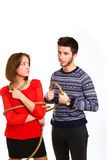 Muchacho enojado y muchacha atados con la cuerda aislada en el fondo blanco fotos de archivo