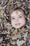 Muchacho enterrado en hojas Fotos de archivo