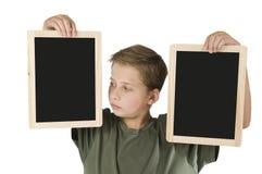 Muchacho entre dos tableros negros dejados Fotos de archivo