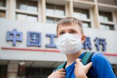 Muchacho europeo en una máscara protectora en una calle en Pekín Imagen de archivo libre de regalías
