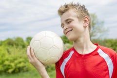 Muchacho feliz activo, divirtiéndose al aire libre, jugando a fútbol en verano juguetón Imagen de archivo