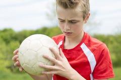 Muchacho feliz activo, divirtiéndose al aire libre, jugando a fútbol en verano juguetón Fotos de archivo