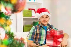 Muchacho feliz adolescente con los regalos de Navidad Imagen de archivo