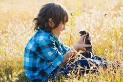 Muchacho feliz adolescente que juega con el animal doméstico de la rata al aire libre Fotos de archivo libres de regalías