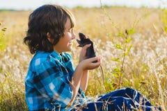Muchacho feliz adolescente que juega con el animal doméstico de la rata al aire libre Foto de archivo